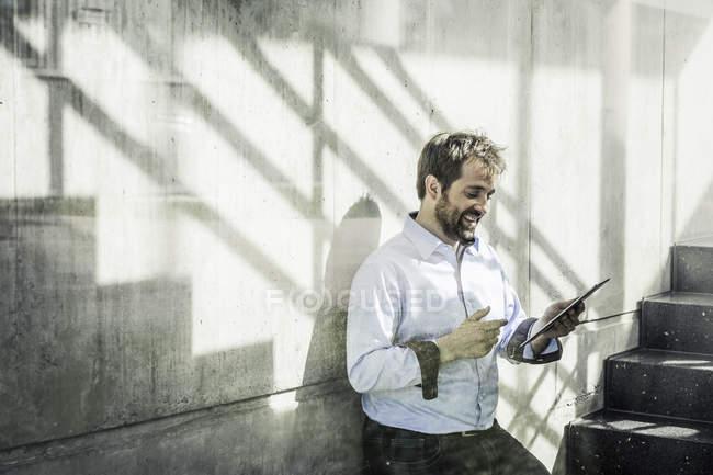 Бізнесмен в офісі stairway дивлячись на цифровий планшетний — стокове фото