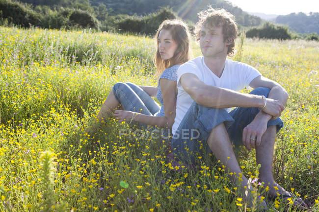 Романтическая молодая пара, сидящая спиной к спине на диком цветочном поле, Майорка, Испания — стоковое фото