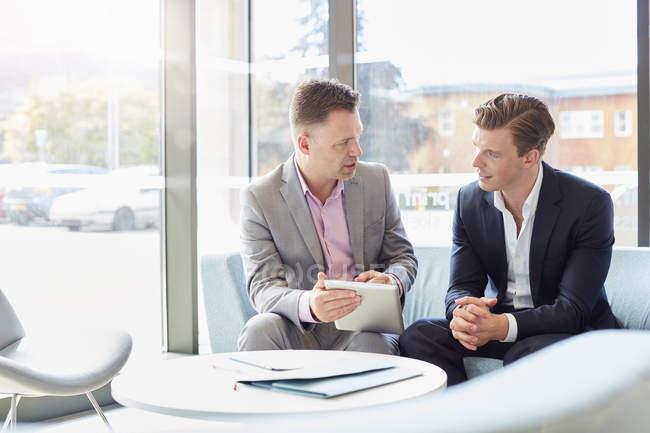Deux hommes d'affaires utilisant une table numérique lors d'une réunion de bureau — Photo de stock