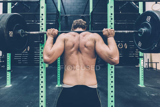 Rear view of male cross trainer weightlifting barbell in gym — Stock Photo