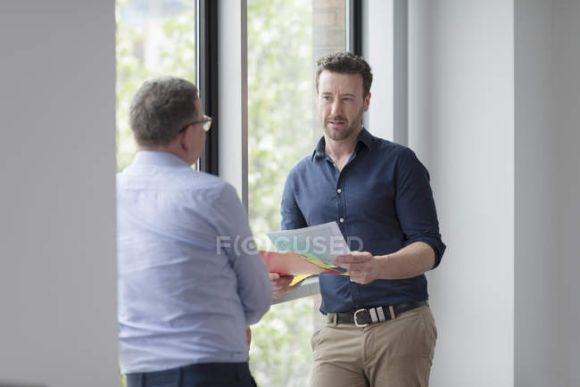 Male colleagues at office window standing and talking while holding paper documents — Stock Photo