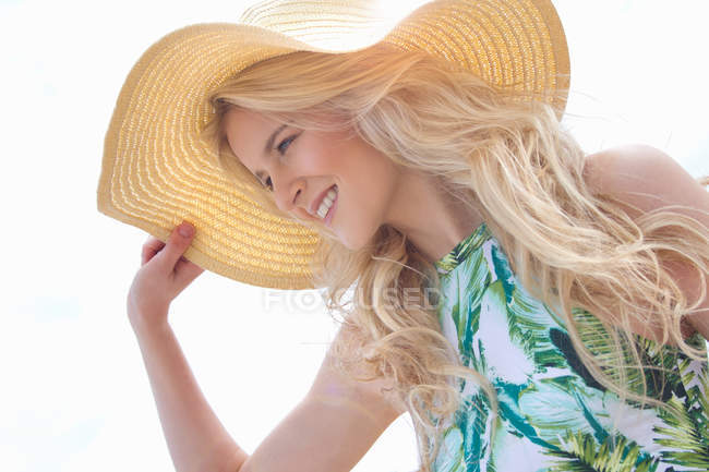 Portrait of young woman holding onto sunhat — Stock Photo
