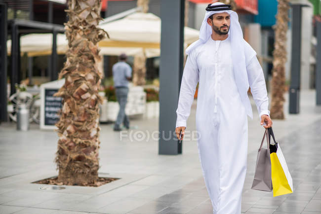 Homme portant des vêtements traditionnels du Moyen-Orient en se promenant rues transportant sacs à provisions, Dubai, United Arab Emirates — Photo de stock