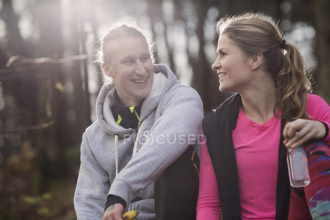 Couple wearing sports clothing holding water bottle sitting face to face smiling — Stock Photo