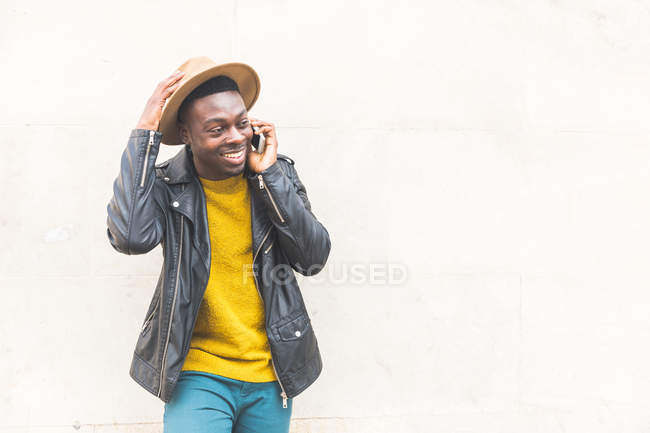 Man wearing hat leaning against wall making telephone call smiling — Stock Photo
