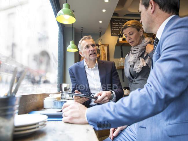 Бизнесмены и женщина, беседующие в витрине ресторана — стоковое фото