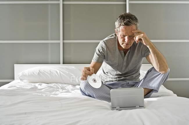 Senior homme assis tenant le Cd et regarde fixement portable — Photo de stock