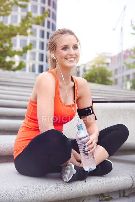 Woman sitting cross legged holding water bottle looking at camera smiling — Stock Photo