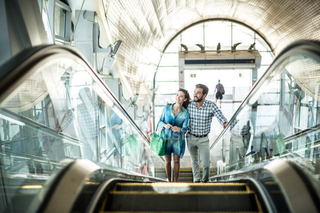 Couple de touristes remontant escalator dans shopping mall, Dubai, United Arab Emirates — Photo de stock