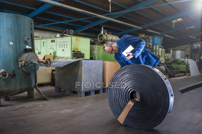 Man in manufacturing plant examining rolled up rubber product — Stock Photo
