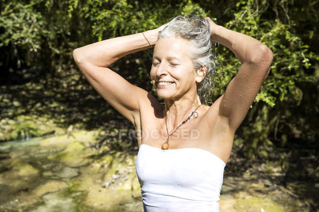 Woman wearing swimsuit tying hair — Stock Photo