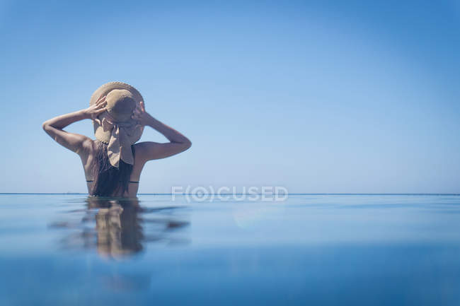 Rear view of young woman standing in blue sea with hands on sunhat, Villasimius, Sardinia, Italy — Stock Photo