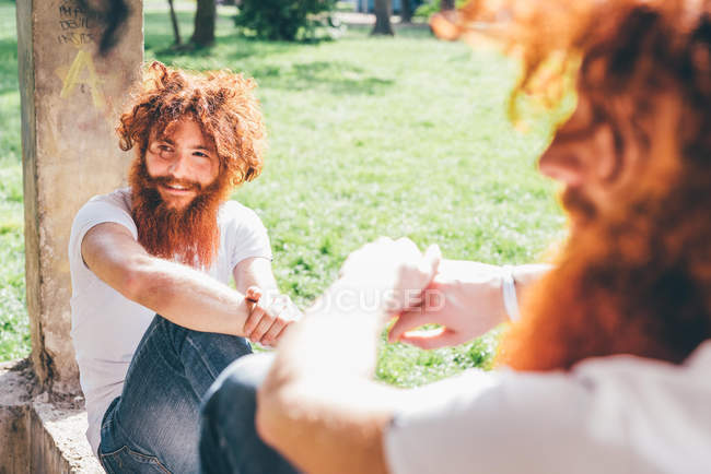 Young male hipster twins with red beards sitting on park wall — Stock Photo