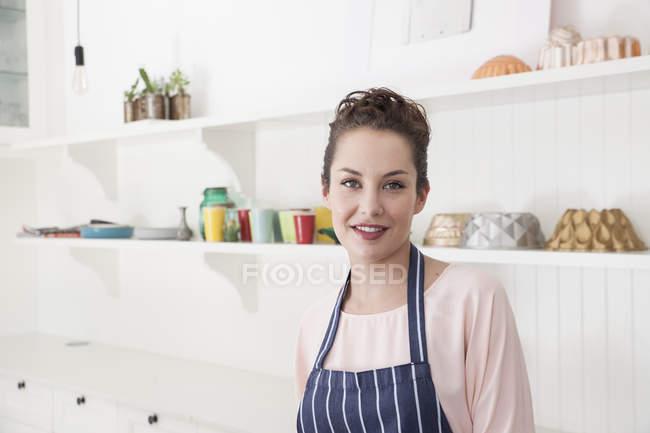 Портрет молодої жінки кухні, дивлячись на камеру — стокове фото