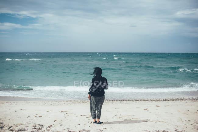 Вид сзади женщины на пляже, глядя на океан, Sorso, Сассари, Италия — стоковое фото