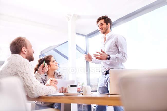 Jeune homme d'affaires faisant une présentation à l'équipe d'affaires au bureau — Photo de stock