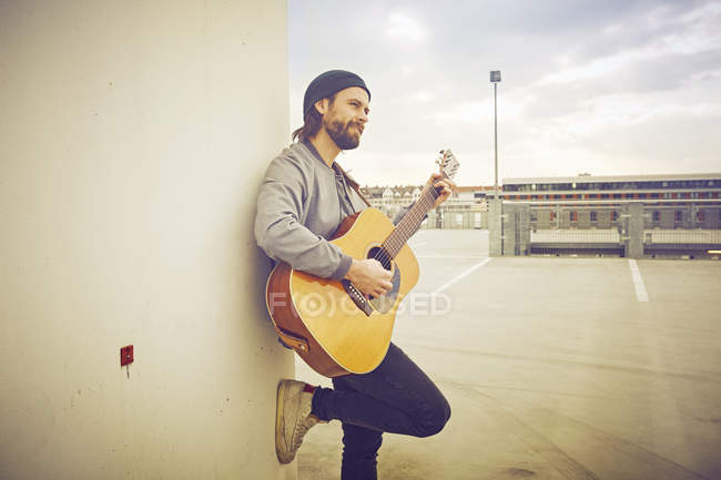 Mid adult man playing acoustic guitar on rooftop parking lot — Stock Photo