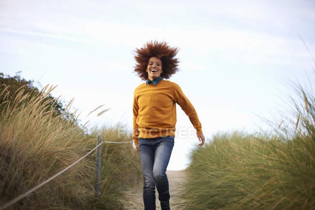 Жінка працює вниз трав'янистих дюн — стокове фото