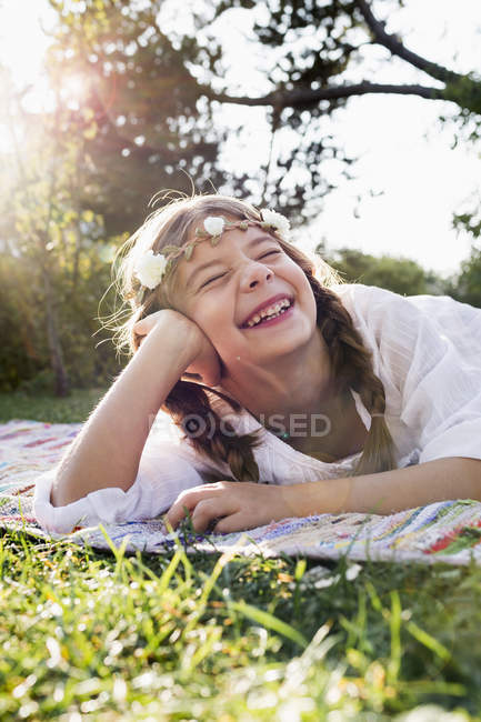 Girl with flowers round head laughing with eyes closed — Stock Photo