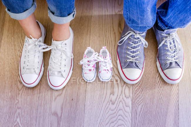 Blick auf Babyschuhe zwischen männlichen und weiblichen Füße abgeschnitten — Stockfoto