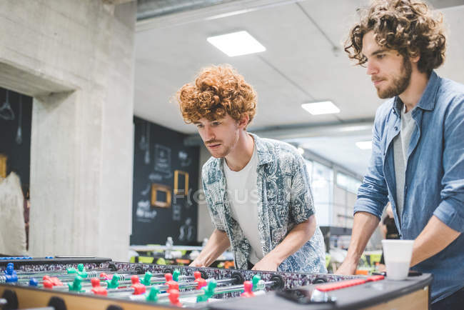 Co-workers playing foosball at break together — Stock Photo