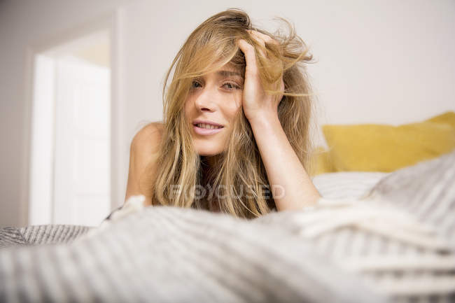Portrait of beautiful woman lying on bed with hand in long blond hair — Stock Photo