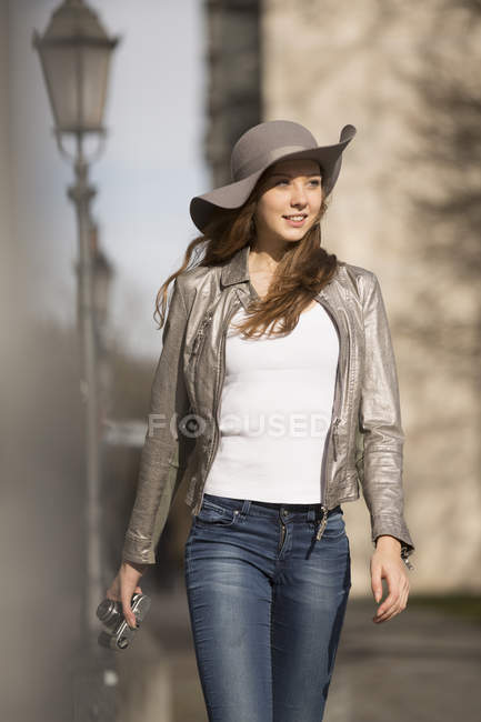 Женщина в гибкой шляпе наслаждается прогулкой по городу — стоковое фото