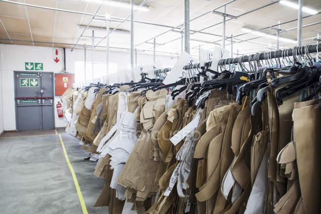 Padrões de costura pendurados no trilho de roupas na sala de amostra de fábrica de costura — Fotografia de Stock