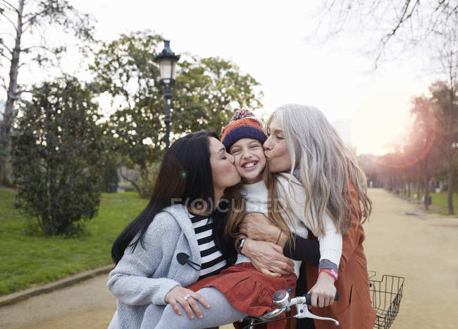 Mother and grandmother kissing smiling girls cheeks — Stock Photo