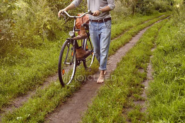 Blick auf Mann, der Fahrrad auf Feldweg schiebt — Stockfoto