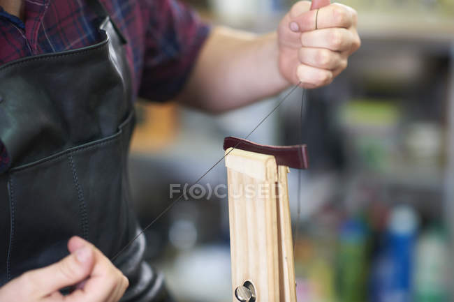Male worker in leather workshop, sewing up watch strap, mid section, close-up — Stock Photo