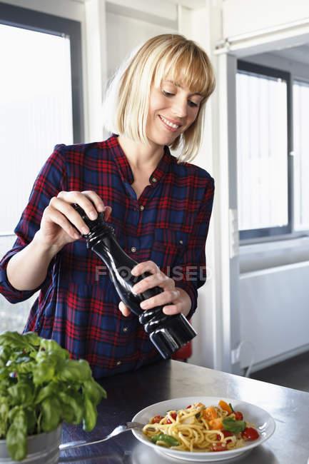 Frau würzen Schüssel mit Pasta in der Küche — Stockfoto