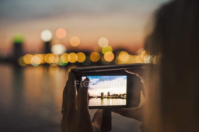 Young woman photographing view with smartphone, close-up of screen — Stock Photo