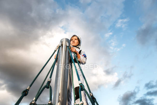 Boy in astronaut costume gazing at top of climbing frame against dramatic sky — Stock Photo