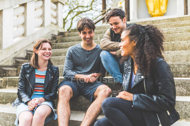 Four young adult friends on stairway chatting in Battersea Park — Stock Photo