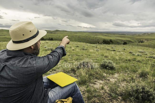 Мужчина-турист указывает на пейзаж, Коди, Вайоминг, США — стоковое фото