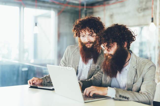 Männliche Hipster-Zwillinge arbeiten am Laptop am Schreibtisch — Stockfoto
