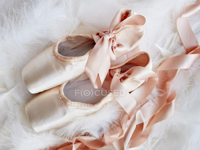 Ballet slippers with ribbons on fluffy plaid — Stock Photo