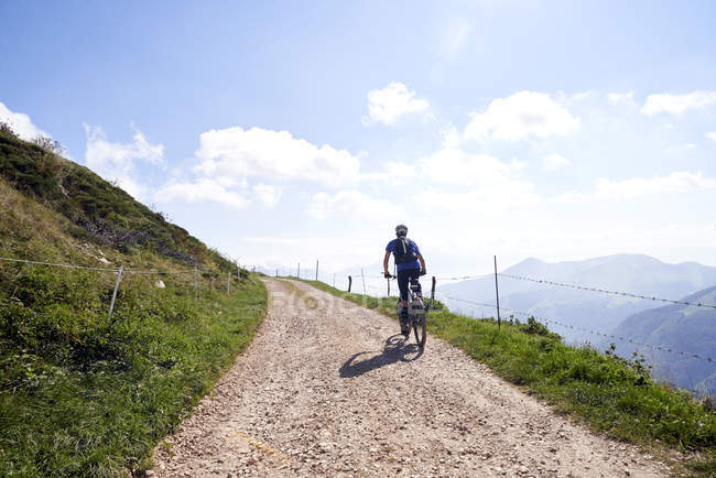 Rear view of cyclist cycling on dirt track in mountains — Stock Photo