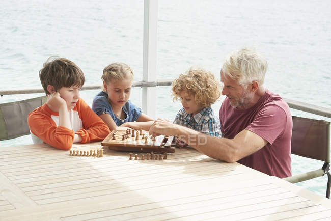 Grandfather and grandchildren playing chess — Stock Photo