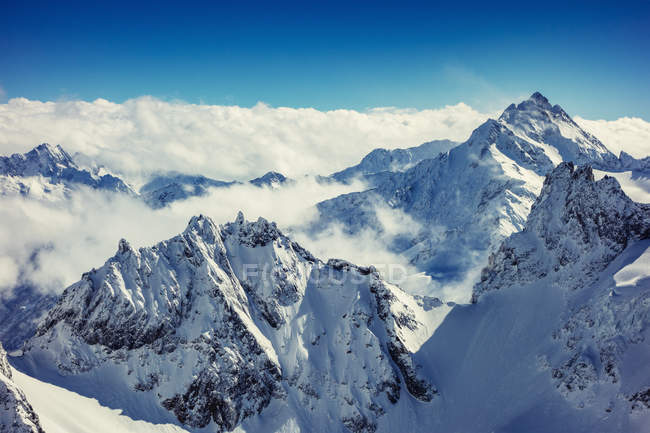 Basse nuvole sopra cime innevate — Foto stock