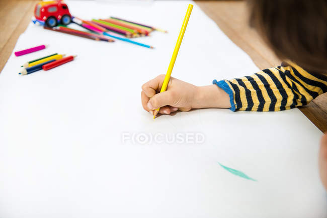 Hand of boy lying on floor drawing on long paper — Stock Photo