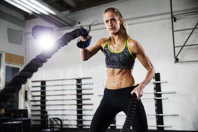 Femme d'entraînement avec corde de combat dans la salle de gym — Photo de stock