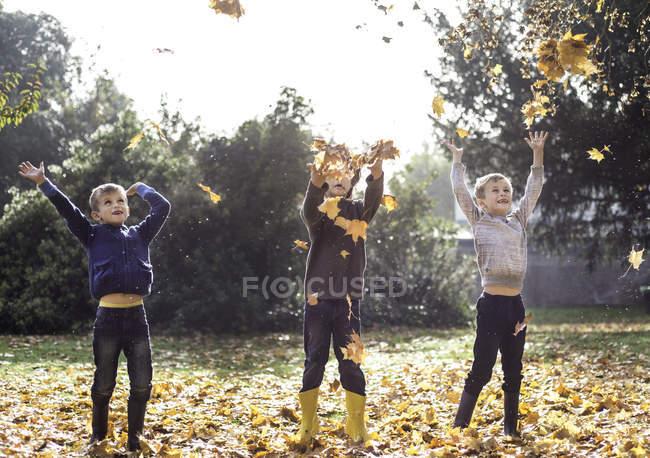 Tre ragazzi all'aperto, lanciando foglie autunnali — Foto stock