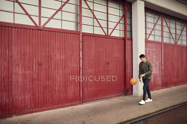 Young man in urban area, bouncing basketball, Bristol, UK — Stock Photo