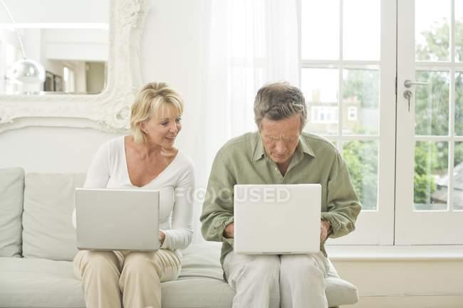 Casal no sofá usando laptops — Fotografia de Stock