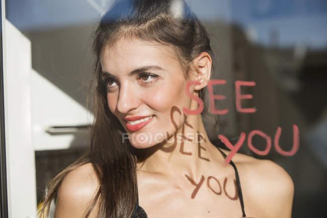 Giovane donna che guarda fuori dalla finestra, 'ci vediamo' scritto sulla finestra con il rossetto — Foto stock
