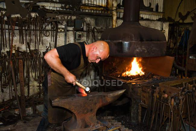 Caucasian male blacksmith at work in smith — Stock Photo