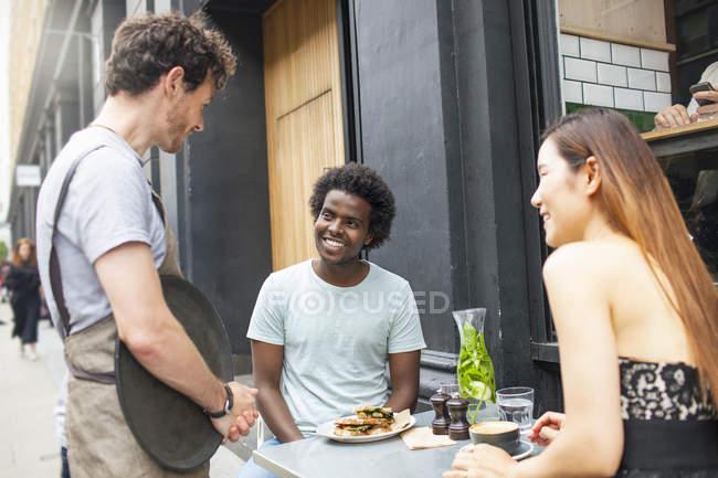 Waiter serving couple at city sidewalk cafe — Stock Photo