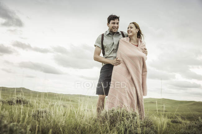 Happy young woman wrapped in blanket with boyfriend in landscape, Cody, Wyoming, USA — Stock Photo